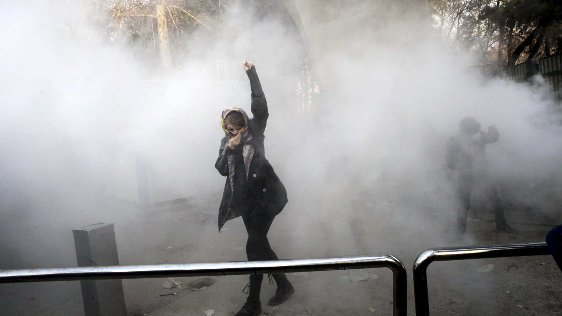 A university student attends a protest inside Tehran University while a smoke grenade is thrown by anti-riot Iranian police, in Tehran, Iran (AP)
