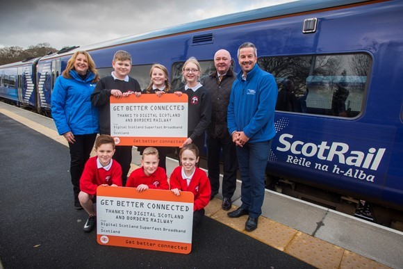 Glynis Follon (Digital Scotland Community Project Officer), P6 and P7 Pupils from Tweedbank Primary School, Councillor Mark Rowley and Robert Thorburn (Openreach Fibre Partnership Director for Scotland) celebrate fibre availability along the Borders Railw