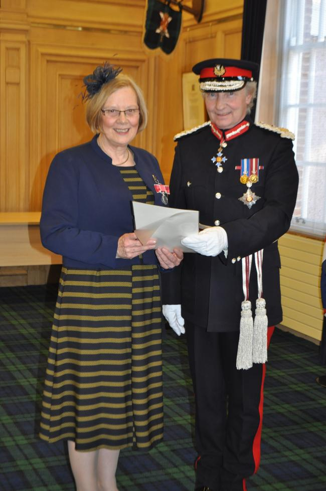 Sandra Plasting collecting her British Empire medal