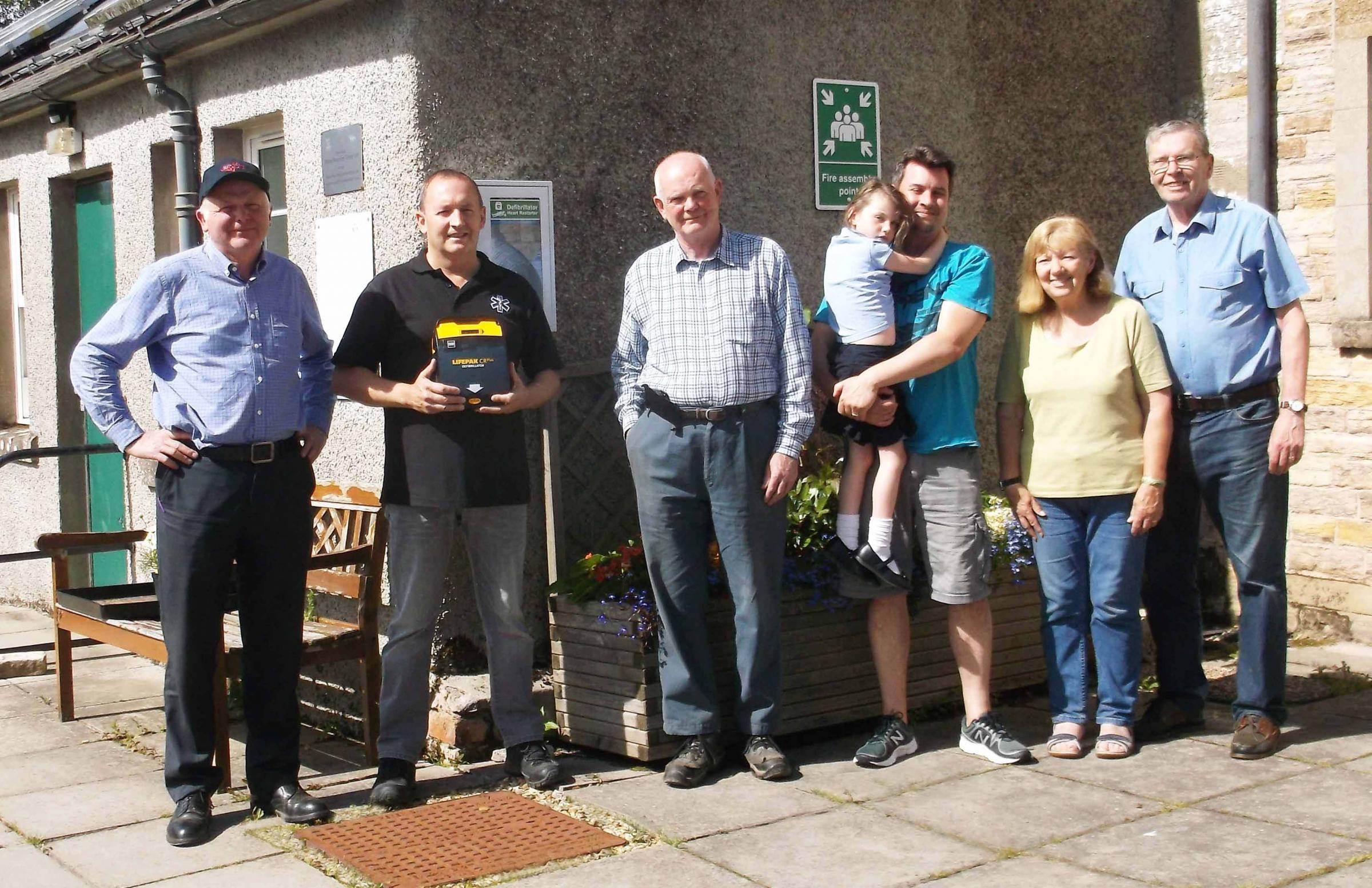 Ian Rose (William Rose and Sons), paramedic Tony Haley, William Rose, local resident Adam Bullough and daughter Ellie and Cilla and Alan Davidson with the new defibrillator
