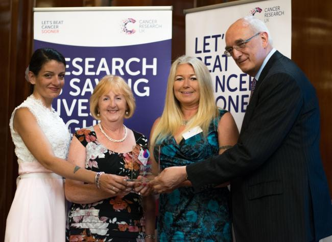 Cancer Research UK Peebles Shop volunteers (L-R) Florence Charlotte, Lorna Duncan and Assistant Manager Debby Strain are presented with the charity's Flame of Hope Shop Of The Year Award by Chairman Sir Leszek Borysiewicz. Photo: Tara Griffin