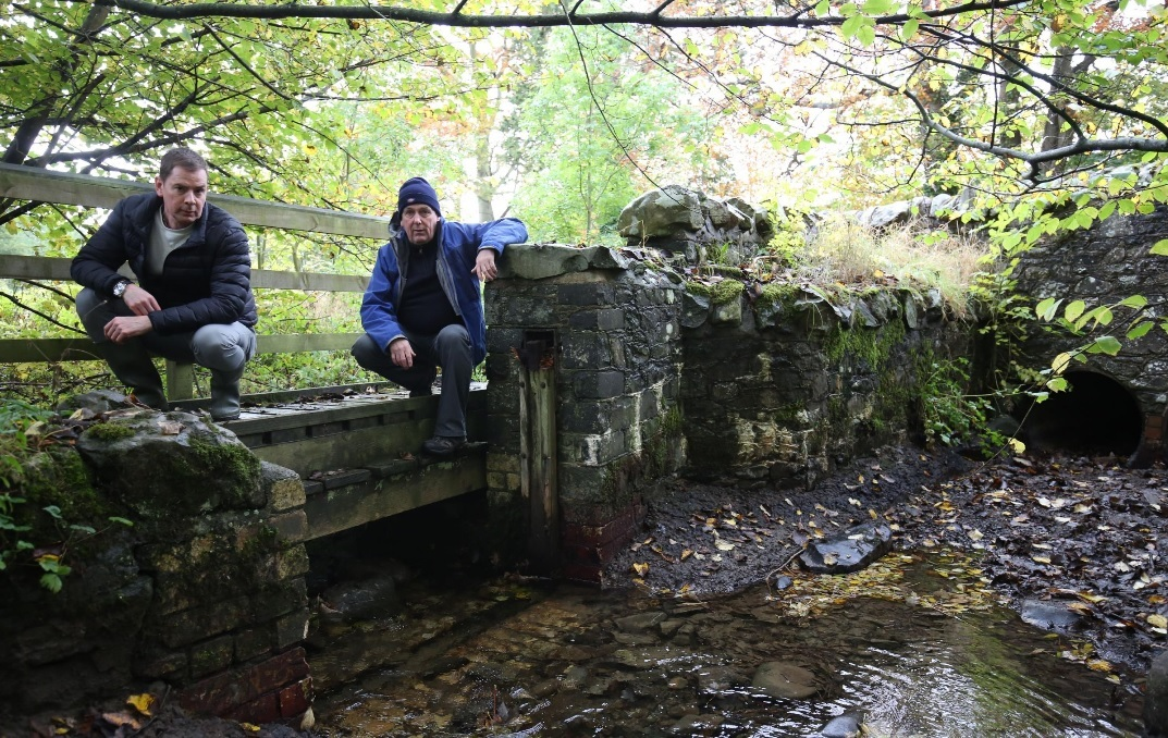Allan Graham and George Meikle pictured at the site of the sluice gate in Innerleithen in 2016 after it had been targeted a number of times. The gate had been sawn off by a chainsaw and washed down the river. Photo: Helen Barrington