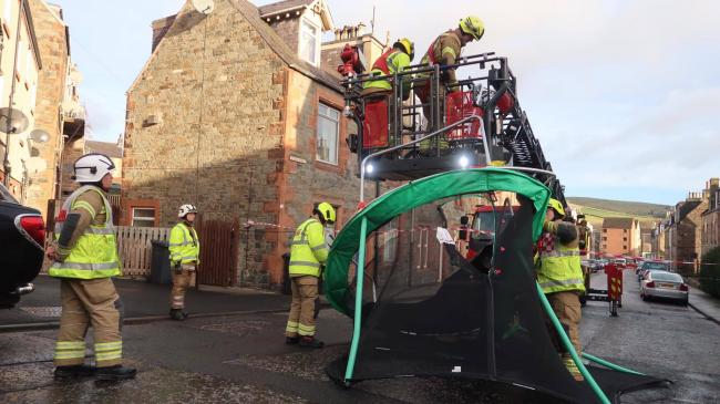 Firefighters bringing down the trampoline. Photo: Ian Macey