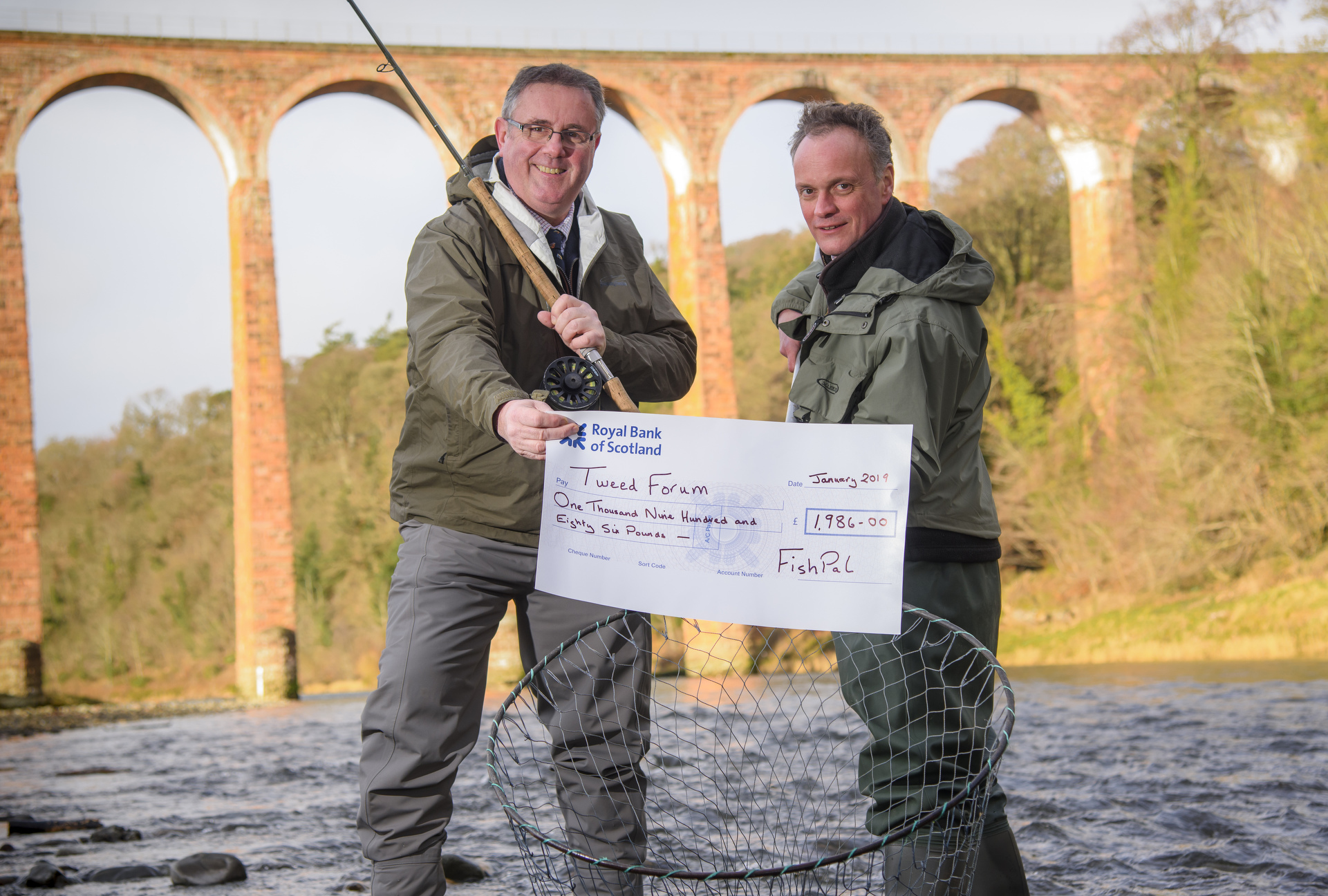 Mark Cockburn, CEO FishPal, presents Luke Comins, Director, Tweed Forum, with a £1,986 donation from anglers who fish on the River Tweed. Photo: Phil Wilkinson